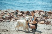 Photo young asian woman embracing dog on beach in front of sea
