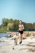 Sportlerin joggt tagsüber mit Hund am Strand
