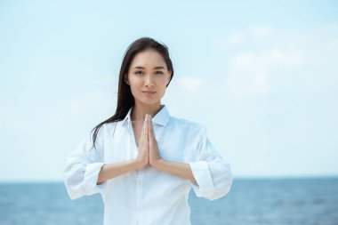 focused asian woman doing namaste mudra gesture in front of sea
