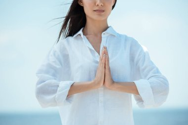 Cropped image of asian woman doing namaste mudra gesture on beach stock vector
