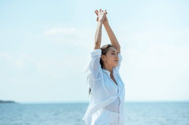 attractive asian woman with closed eyes standing with wide arms in front of sea