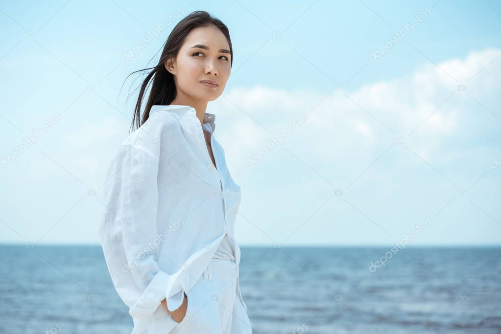 young asian woman with hands in pockets looking away by sea