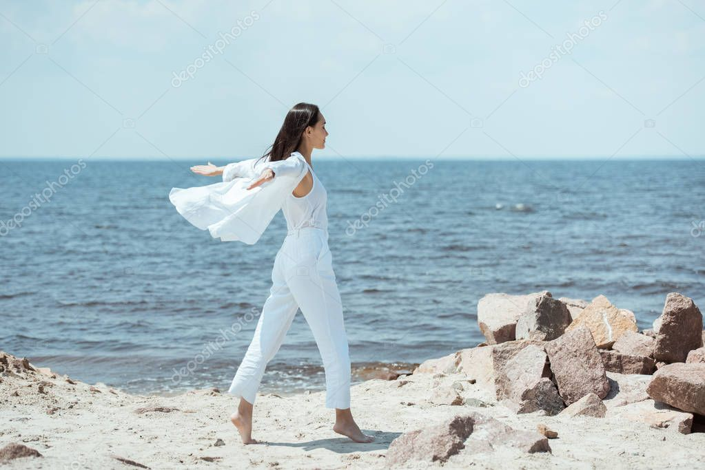 side view of asian young woman enjoying sea with arms outstretched on beach