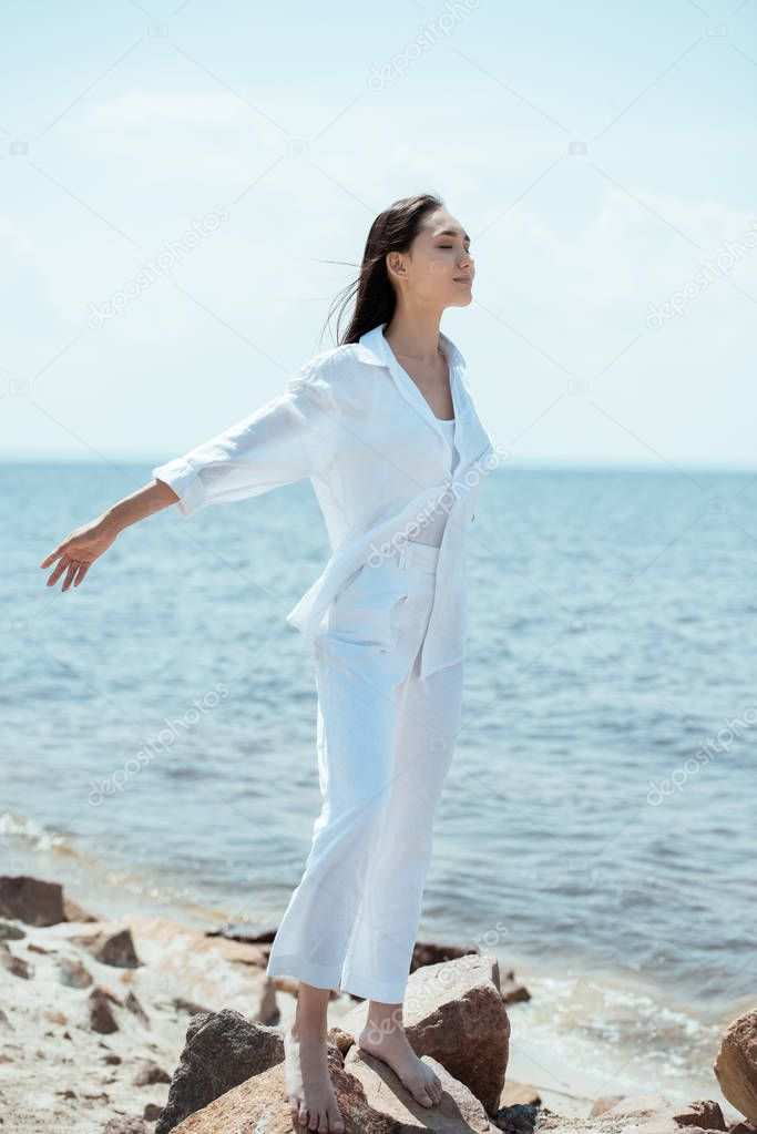 happy asian woman with closed eyes enjoying sea and standing with arms outstretched on beach