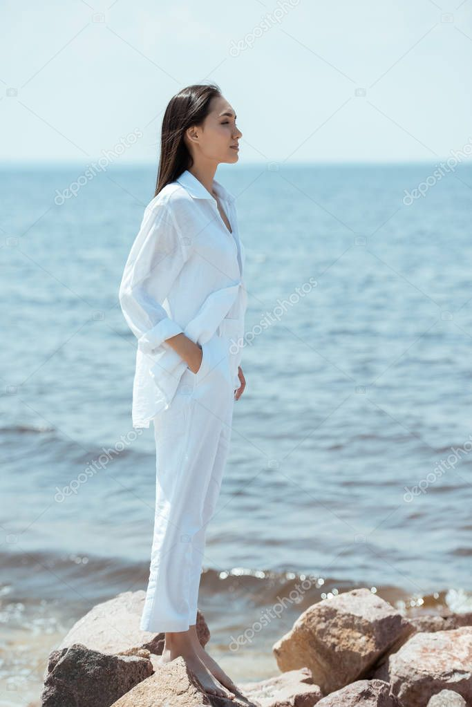 side view of attractive asian woman with hand in pocket standing on beach by sea