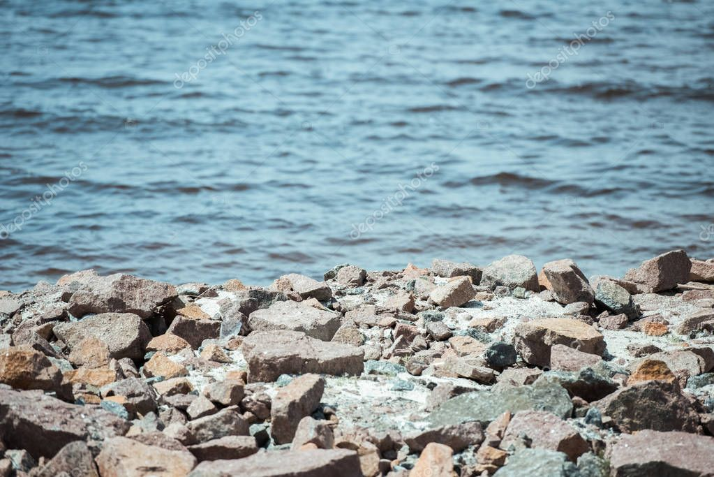 selective focus of rocky beach and wavy sea behind during daytime