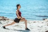 Seitenansicht des jungen asiatischen weiblichen Athleten machen Ausfallschritte am Strand