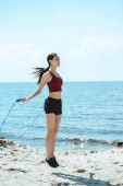 Fotografie asian sportswoman doing exercise with jump rope on beach