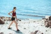Mladá sportovkyně dělat cvičení s protahováním kapely na pláži