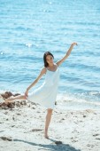 focused asian woman in white dress dancing on beach by sea