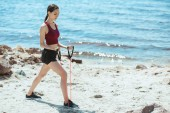 side view of young sportswoman doing exercise with stretching band on beach