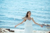 Photo happy asian woman in white dress with wide arms standing by sea