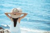 zadní pohled na ženy v bílých šatech a slaměný klobouk stojící před moře