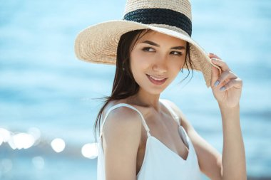 Selective focus of attractive asian woman in straw hat looking away stock vector