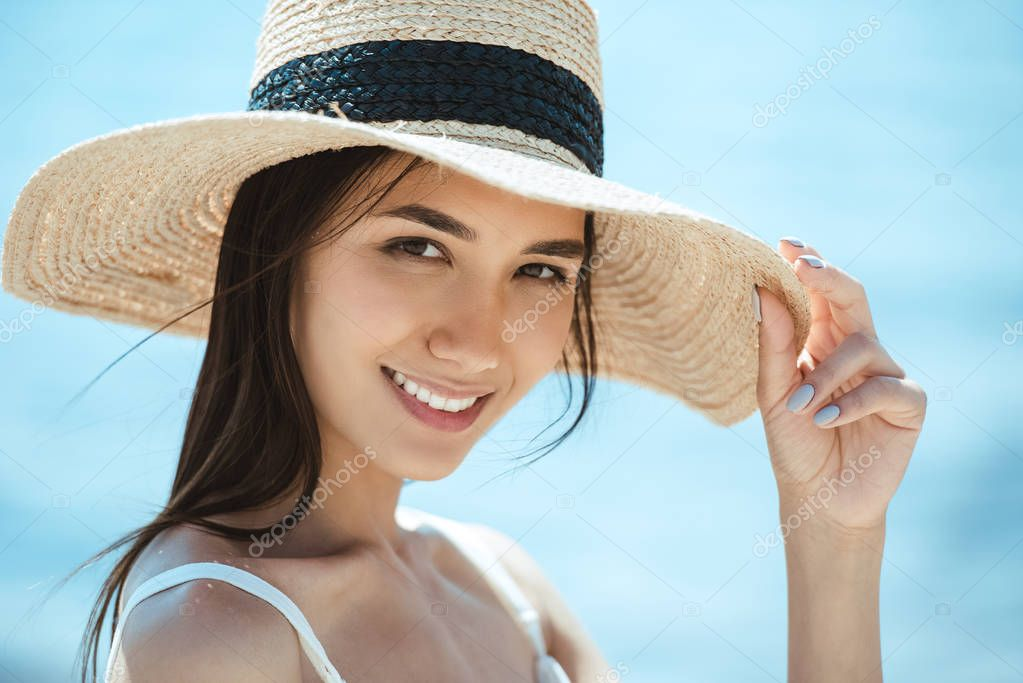 close up portrait of attractive asian woman in straw hat looking at camera