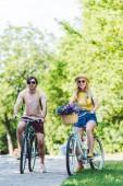 Fotografia giovane coppia bicicletta retrò nel parco il giorno di estate