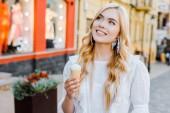 portrét krásné usměvavé ženy se zmrzlinou v ruce koukal na ulici
