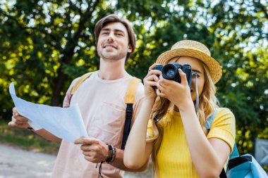 portrait of couple of tourists with map and photo camera in park