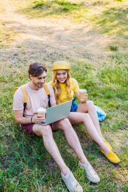 Young couple with coffee to go using laptop in park stock vector