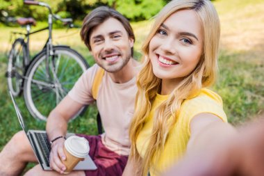 camera point of view of smiling couple taking picture in summer park