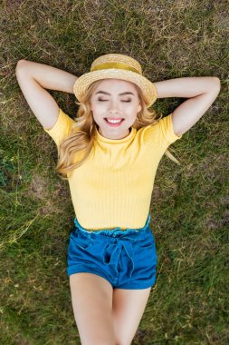 overhead view of smiling young woman in hat resting on green grass in park