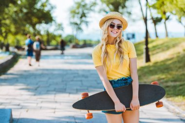 Portrait of smiling blond woman in sunglasses and hat with longboard in hands on street stock vector
