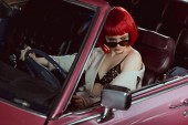 high angle view of beautiful woman in sunglasses, bra and trench coat driving classic car and looking away