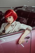Fotografie beautiful young woman in red wig holding cigarette and sitting in vintage car