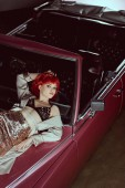 high angle view of beautiful stylish girl lying on vintage car and looking at camera