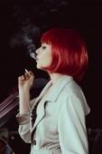Seitenansicht des schönen Mädchens mit roter Perücke und stylischem Trenchcoat beim Zigarettenrauchen im Auto