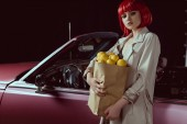 Fotografie woman in red wig and stylish trench coat holding paper bag with lemons and looking at camera while standing near retro car