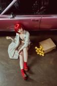 Hochwinkelaufnahme der schönen Mädchen in stilvollem Trenchcoat mit Zitrone und Blick in die Kamera, während sie in der Nähe von Retro-Auto sitzen