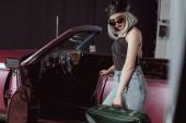 Fotografia elegante ragazza bionda in occhiali da sole e berretto che tiene retro valigia e che guarda lobbiettivo mentre levandosi in piedi vicino allautomobile marrone rossiccio