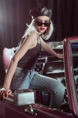 Fotografie stylish blonde girl in black beret and sunglasses opening classic car and looking at camera