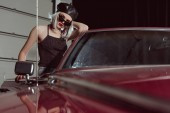 Fotografie fashionable blonde woman in black beret and sunglasses leaning at maroon car and looking at camera