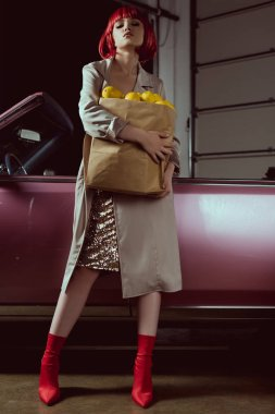 low angle view of beautiful blonde woman in red wig and stylish trench coat holding paper bag with lemons and looking at camera while standing near classic car