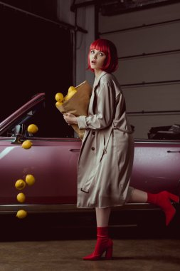 girl in red wig and stylish trench coat holding paper bag with falling lemons near retro car