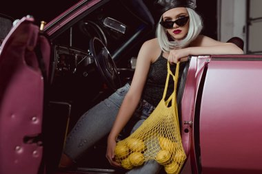 stylish blonde girl in beret and sunglasses holding string bag with lemons while sitting in car