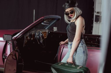 stylish blonde girl in sunglases and beret holding retro suitcase and looking at camera while standing near maroon car