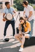 Fotografia Giovane e felice multirazziale maschili e femminili musicisti di strada in città