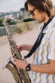 Fotografia Giovane con il sassofono eseguendo sulla strada soleggiata città