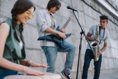 Fotografie Multiracial young musical band with guitar, drum and saxophone performing on street