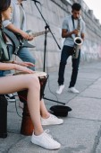 Fotografie Talented street musicians with guitar, drum and saxophone performing in city