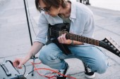 Photo Young man adjusting guitar amplifier while performing on street