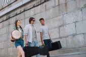 Fotografia Multiracial musical band walking and carrying musical instruments on sunny city street