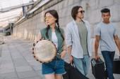 Fotografia Squadra di giovani amici maschii e femminili a piedi e trasportare strumenti musicali in ambiente urbano