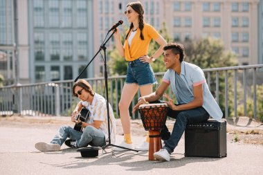 Team of young friends performing and singing in urban environment