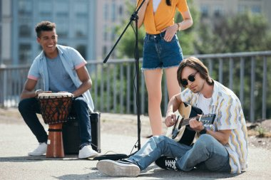 Young and happy street musicians playing music and singingin city