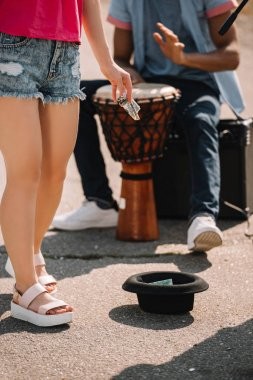 Passing by woman giving money to city street drummer playing djembe