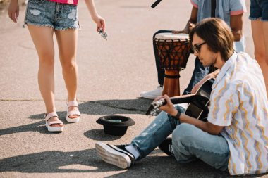Young happy buskers playing an improvised concert at city street and receiving money